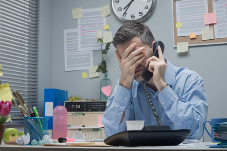 messy: Stressed employee on the phone touching his forehead. Stock Photo