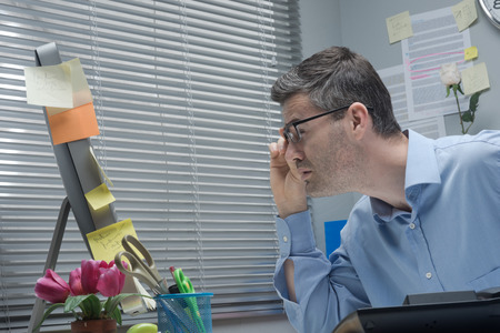 computer problem: Businessman holding glasses and staring at computer close-up, vision problems concept. Stock Photo