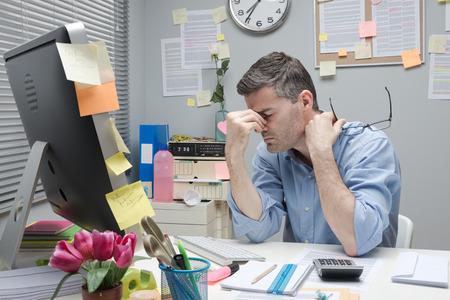 Depressieve vervelen kantoormedewerker aan zijn bureau met een bril.