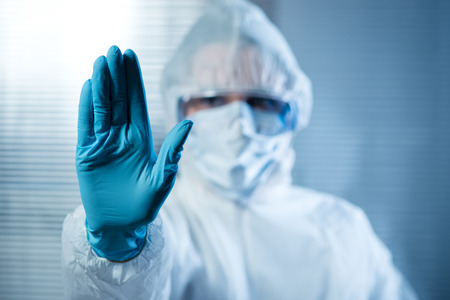 Scientist with hand raised in hazmat protective suit, stop concept.