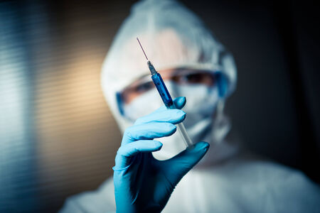 hazmat: Researcher in hazmat protective suit preparing a syringe for injection. Stock Photo