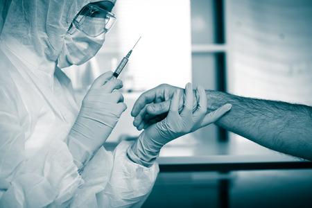 infective: Doctor que inyecta la medicaci�n en el brazo del paciente usando una jeringa.