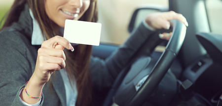 Young smiling woman driving a car and holding a business identification card or drivers license. Stock Photo