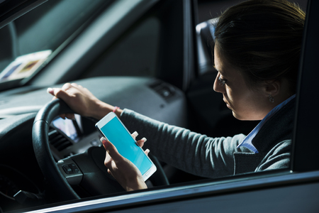 female driver: Young lost female driver using mobile phone while driving at night.