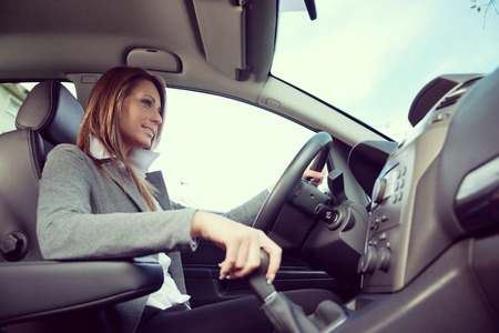 gearstick: Young attractive woman driving, holding gear stick and smiling.