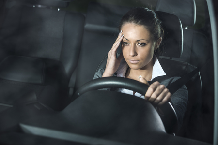 Tired woman driving at night with headache touching temples.