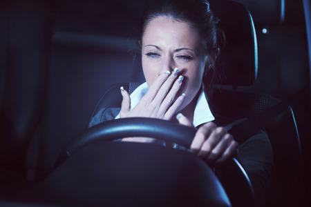 Afgeleid uitgeput vermoeide vrouw het besturen van een auto 's avonds laat.