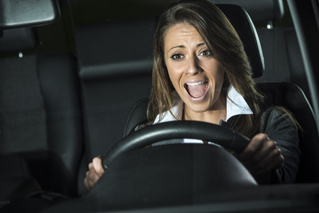 Young terrified woman driving and having a car accident at night. Stock Photo