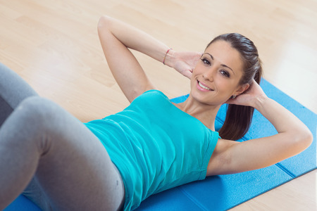 muscle toning: Attractive woman doing abs workout at gym for muscle toning and flat stomach. Stock Photo