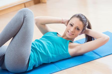 flat stomach: Donna attraente che fa allenamento addominali in palestra per la tonificazione muscolare e pancia piatta.