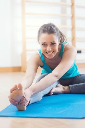 魅力的な女性の足のマットの上のストレッチ体操を行うジムでワークアウトします。