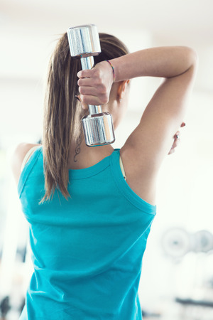 back training: Attractive woman working out with dumbbells rear view.