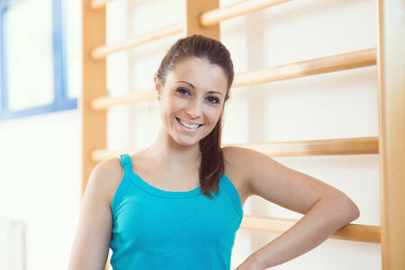 wall bars: Attractive smiling woman at gym leaning to wood wall bars. Stock Photo