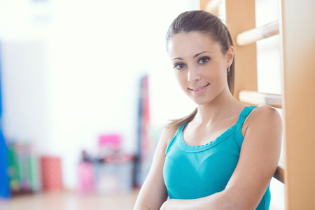 wall bars: Attractive smiling woman at gym leaning against wood wall bars.