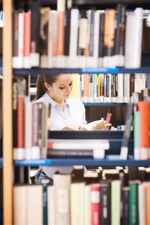 research study: Young smiling student at the library searching for books