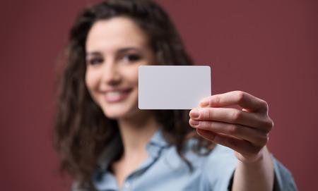 Jonge glimlachende vrouw die een blanco visitekaartje