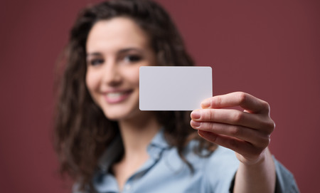 Young smiling woman holding a blank business card Stock Photo - 36877156