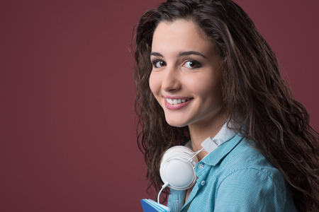 Smiling teenager girl with headphones looking at camera
