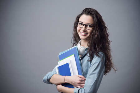 Beautiful student girl posing with books and smiling at camera Stockfoto