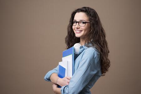 Mooie jonge tiener meisje student poseren met notebooks en glimlachen op camera