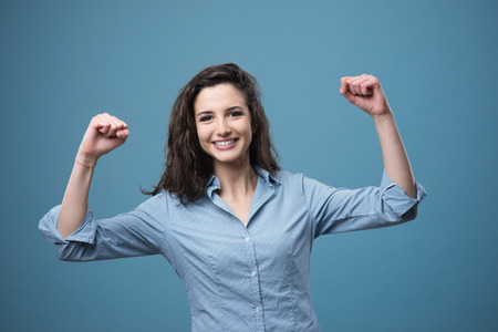 strong toughness: Cheerful young woman smiling with raised fists