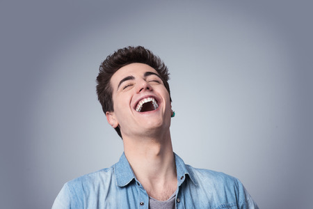 loud: Funny smiling guy laughing out loud with closed eyes