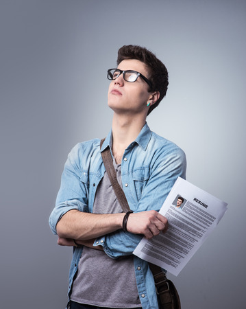 Young pensive man holding his resume applying for a job Stock Photo