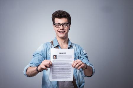 estudiante: Hombre sonriente joven que sostiene su curr�culum solicitar un empleo