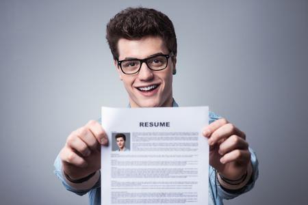 彼の履歴書は、仕事を適用することを保持している笑みを浮かべて青年
