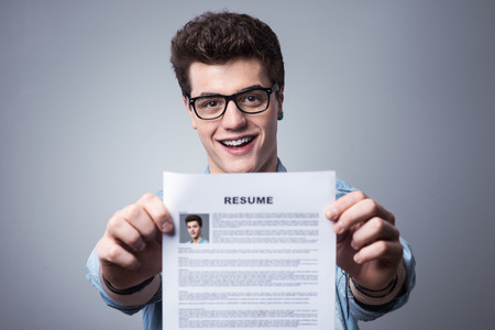 Young smiling man holding his resume applying for a job