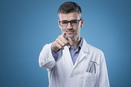 health service: Confident smiling doctor with lab coat pointing an looking at camera Stock Photo