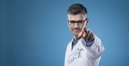 health care decisions: Confident smiling doctor with lab coat pointing an looking at camera Stock Photo