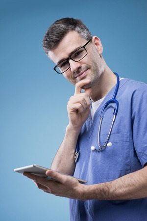 Confident young doctor using a touch screen digital tablet photo
