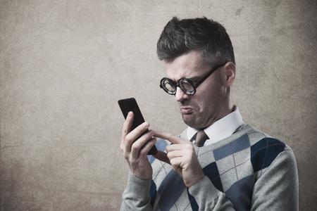 frustrace: Funny bezradný hloupý kluk má problémy s jeho smartphone Reklamní fotografie