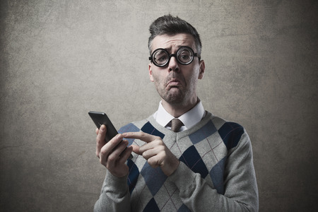 Funny clueless dumb guy having troubles with his smartphone photo