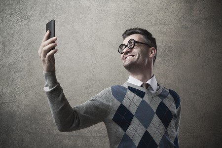 Funny guy with glasses taking a self picture with a smartphone photo