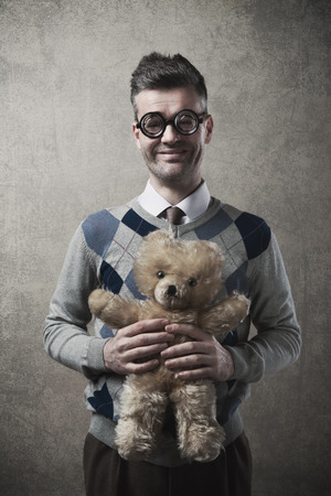 cute guy: Childish funny guy with glasses holding a cute teddy bear