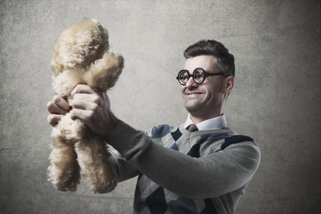 childish: Childish funny guy with glasses holding a cute teddy bear