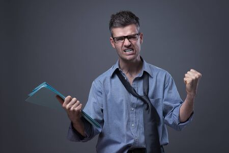 untidy: Angry untidy businessman with files snarling with fist raised