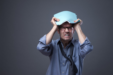 untidy: Angry untidy businessman holding files over head snarling
