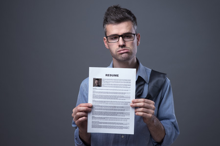 looking for a job: Sad businessman looking for a job and holding his resume Stock Photo