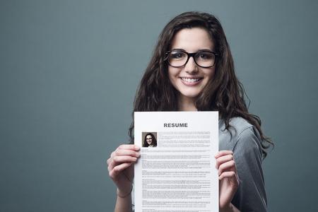 Mujer alegre sonriente joven sosteniendo su hoja de vida Foto de archivo