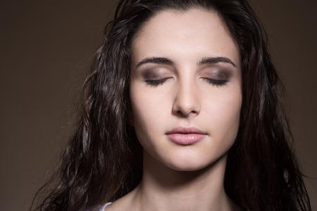 Ontspannen vrouw die zich met gesloten ogen op een donkere achtergrond