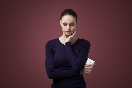 Sad woman looking down and holding a mobile phone