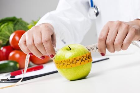 Voedingsdeskundige meten van een appel met meetlint, dieet en gewichtsverlies concept van Stockfoto