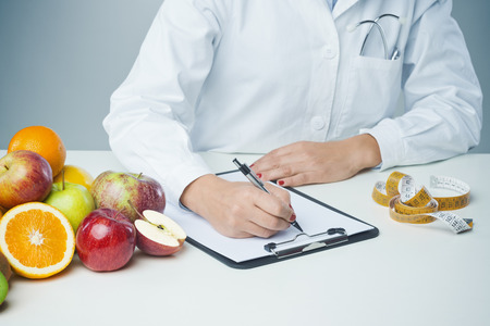 dietology: Female nutritionist at work writing documents on a clipboard with fresh fruit on foreground Stock Photo