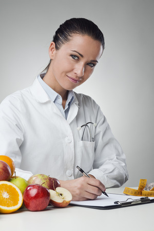dietology: Smiling nutritionist writing medical records with fresh fruit on foreground