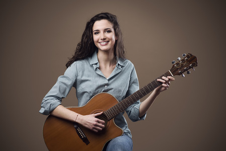 smiling girl: Beautiful young smiling girl playing acoustic guitar Stock Photo