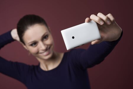 self   portrait: Young smiling woman taking a self portrait with her mobile phone
