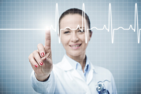 systole: Female doctor pressing a button on a touch screen interface